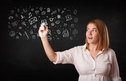 Jonge vrouw die en pictogrammen trekken schetsen Stock Foto's