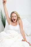 Jonge vrouw die en zich in bed uitrekt geeuwt Royalty-vrije Stock Afbeeldingen