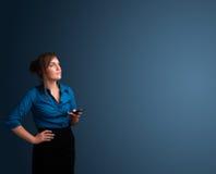 Jonge vrouw die en zich op haar telefoon met exemplaarruimte bevinden typen Royalty-vrije Stock Fotografie