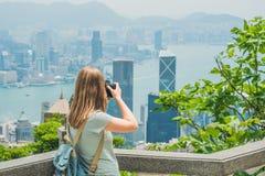 Jonge vrouw die foto's van de haven van Victoria in Hong Kong, China nemen Stock Foto