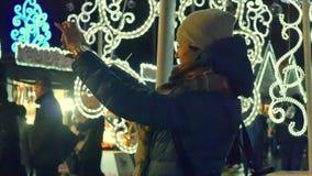 Jonge vrouw die foto van de markt van de Kerstmisstraat op slimme telefoon nemen stock footage