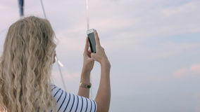 Jonge vrouw die foto van mooie overzeese lagune op smartphone nemen Royalty-vrije Stock Afbeelding