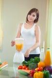 Jonge Vrouw die Fruit Smoothie in Mixer maken royalty-vrije stock foto's