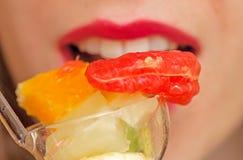 Jonge vrouw die fruitsalade eten Stock Afbeeldingen