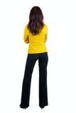 Jonge vrouw die in geel kostuum muur bekijkt. stock foto