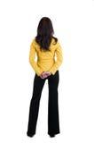 Jonge vrouw die in geel kostuum muur bekijkt. royalty-vrije stock foto's