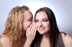 Jonge vrouw die geheim deelt aan haar vriend stock afbeeldingen