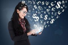 Jonge vrouw die geld maken met tablet online Stock Foto