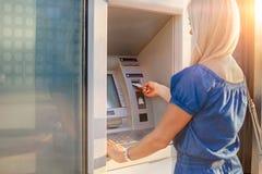 Jonge vrouw die geld van creditcard terugtrekken bij ATM-machine stock foto