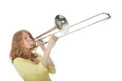 Jonge vrouw die in gele minikleding de trombone spelen stock fotografie