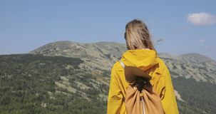 Jonge vrouw die in gele regenjastribunes wandelen in de bergen stock videobeelden