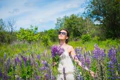 Jonge vrouw die, gelukkig, zich onder het gebied van violette lupines bevinden, het glimlachen, purpere bloemen Blauwe hemel op d stock afbeelding