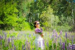 Jonge vrouw die, gelukkig, zich onder het gebied van violette lupines bevinden, het glimlachen, purpere bloemen Blauwe hemel op d Stock Afbeeldingen