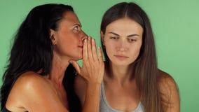 Jonge vrouw die geschokt terwijl haar vrienden die aan haar fluisteren kijken stock video