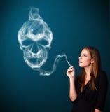 Jonge vrouw die gevaarlijke sigaret met giftige schedelrook roken Stock Foto