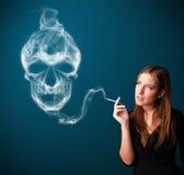 Jonge vrouw die gevaarlijke sigaret met giftige schedelrook roken Royalty-vrije Stock Fotografie