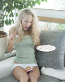 Jonge vrouw die gevallen cake op benen binnenshuis bekijken Royalty-vrije Stock Fotografie