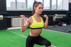 Jonge vrouw die gewichtheffenoefeningen, atletisch wijfje doen die met barbell op haar schouders in gymnastiek hurken stock foto's