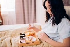 Jonge vrouw die gezond ontbijt in bed eten royalty-vrije stock afbeelding