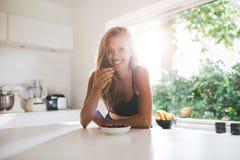 Jonge vrouw die gezond ontbijt eten royalty-vrije stock afbeeldingen