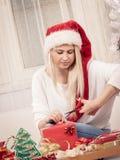 Jonge vrouw die giften voorbereiden op Kerstmis Stock Foto's