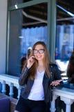 Jonge vrouw die in glazen door smartphone bij straatkoffie spreken Royalty-vrije Stock Foto's