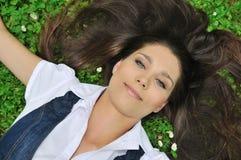 Jonge vrouw die in gras ligt Royalty-vrije Stock Afbeelding