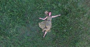 Jonge vrouw die in gras ligt stock videobeelden