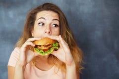 Jonge vrouw die greedily grote smakelijke hamburger eten stock afbeeldingen