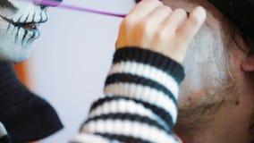 Jonge Vrouw die Griezelige Make-up op Man Gezicht toepassen stock video