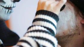 Jonge vrouw die griezelige make-up op man ` s gezicht toepassen in Halloween stock videobeelden