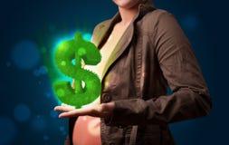 Jonge vrouw die groen gloeiend dollarteken voorstellen Royalty-vrije Stock Foto