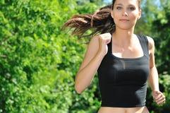 Jonge vrouw die in groen park loopt Royalty-vrije Stock Afbeeldingen