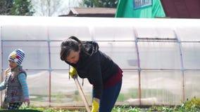 Jonge vrouw die grond voor het planten voorbereiden stock footage
