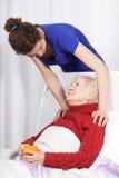 Jonge vrouw die grootmoeder behandelen stock foto