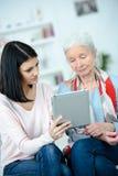 Jonge vrouw die grootmoeder helpen die tablet gebruiken royalty-vrije stock fotografie