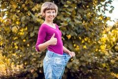 Jonge vrouw die grote losse jeans met in hand appel dragen - gewicht royalty-vrije stock fotografie