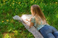 Jonge vrouw die in haar agenda op het gras met bloemen schrijven Achter mening Royalty-vrije Stock Foto's