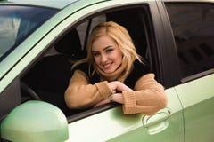 Jonge vrouw die haar auto, dameaandrijving terloops drijft de auto stock fotografie