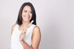 Jonge vrouw die haar die tanden borstelen over witte achtergrond worden geïsoleerd Royalty-vrije Stock Foto's
