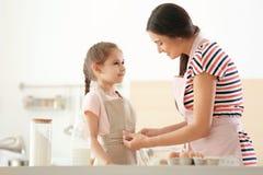 Jonge vrouw die haar dochter helpen om op schort in keuken te zetten Samen makend deeg stock fotografie