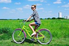 Jonge vrouw die haar fiets in openlucht berijden Stock Foto