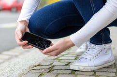 Jonge vrouw die haar gebroken mobiel opnemen Stock Afbeelding