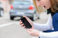 Jonge vrouw die haar gebroken mobiel opnemen Stock Fotografie