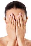 Jonge vrouw die haar gezicht behandelen met haar handen Stock Afbeelding