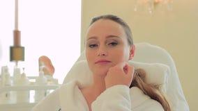 Jonge vrouw die haar gezicht in het bureau van een schoonheidsspecialist strijken stock videobeelden