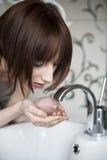 Jonge vrouw die haar gezicht wast Stock Afbeeldingen