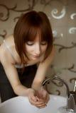 Jonge vrouw die haar gezicht wast royalty-vrije stock foto