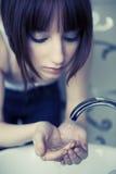 Jonge vrouw die haar gezicht wast royalty-vrije stock afbeelding