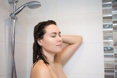 Jonge vrouw die haar haar in douche wassen Royalty-vrije Stock Afbeeldingen